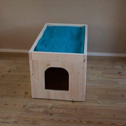Vooraanzicht van kattenbak ombouw model Pers XL. De kattenbak ombouw is geheel gemaakt van steigerhout. Aangekleed met een kleedje.