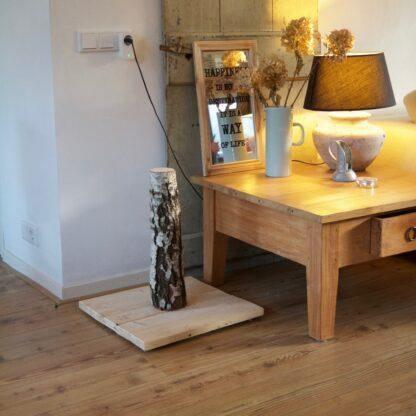 Natuurlijke krabpaal van hout en berk. geplaatst in het interieur.